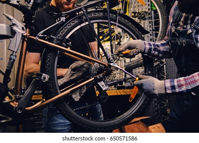 Red head bearded mechanic fixing rear derailleur from a bicycle in a workshop.