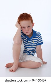 Red head boy wearing blue striped shirt with sad expression on face