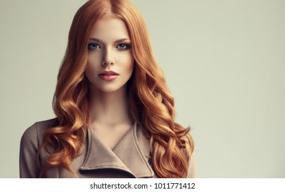 b0eba7ebe8 Red head girl with long and shiny wavy hair . Beautiful model woman with  curly hairstyle