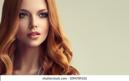 Red head  girl with long  and   shiny curly    hair .  Beautiful  model woman with  wavy hairstyle .
