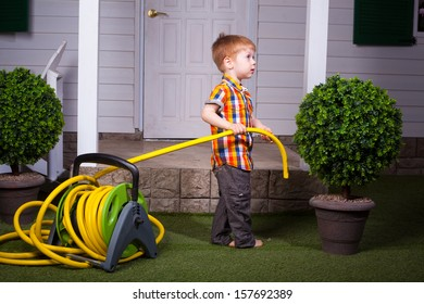 red head little boy in the summer garden with watering hose