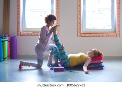 red head pregnant young woman on yoga class indoor with instructor assisting