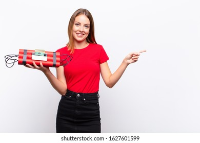 red head pretty woman smiling cheerfully, feeling happy and pointing to the side and upwards, showing object in copy space with a dynamite bomb