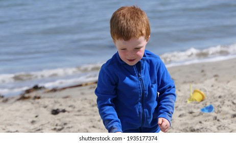 Red headed boy playing with Bucket spade and Digger on a sandy beach
