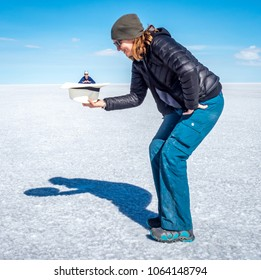 A red headed female stands on the white salt flats, Salar de Uyuni, Bolivia, and appears to be holding a much smaller female in a hat. The smaller woman faces forward. Blue sky fills the horizon.