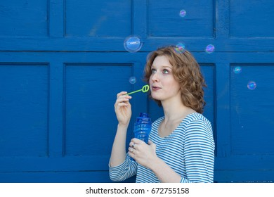 Red headed girl blowing bubbles against blue wall