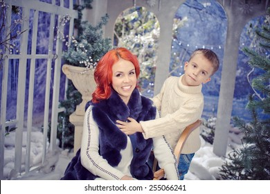 red headed mother and  son  playing.  Winter landscape. Woman wearing fur vest. son wearing white knittiing sweater