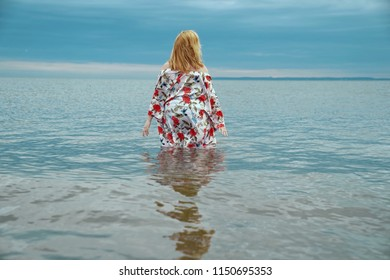 A red headed woman wades in the waves of the Atlantic Ocean