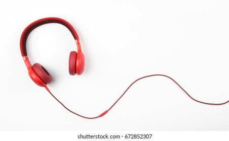 Red headphone and cable isolate on white background.