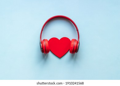 Red headphones with heart shape, top view. Love music concept