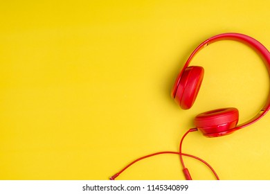Red headphones listens to music on smartphone over yellow background,Music background concept with copy space.