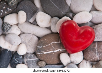 Red heart among river pebble stones