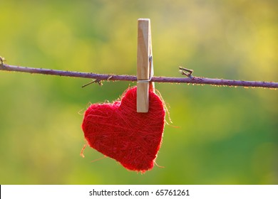 Red heart attached to a clothesline with pin