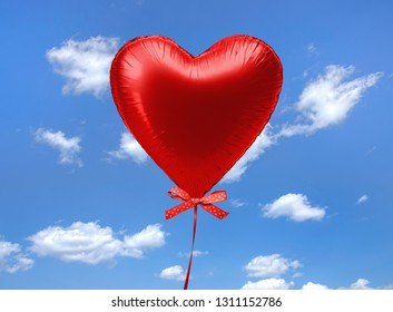 red heart balloon floating in sky with polka dot bow