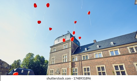 Red heart balloons rise to the sky in front of a castle