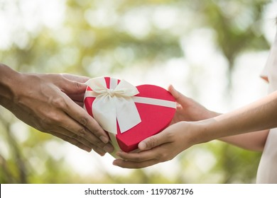 A Red heart box present given from hands to hands on special occasion.