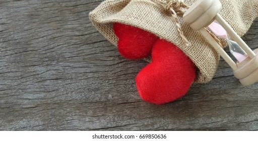 Red heart in brown linen bag with angled sock, on wooden floor.