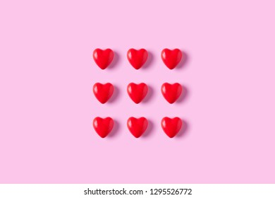 Red heart candies on pink background