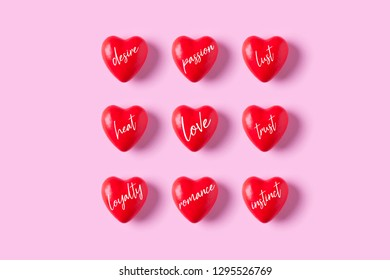 Red heart candies with words about love on pink background