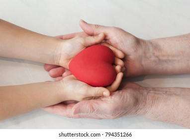 Red heart in child and grandmom hands