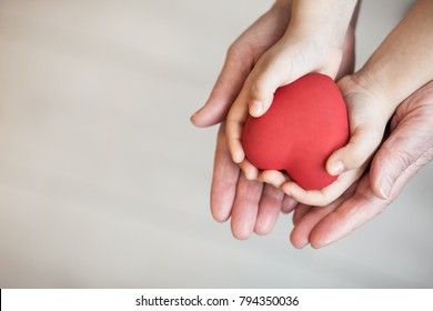 Red heart in child and grandmother's hand
