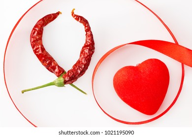Red heart, chili peppers in the shape of heart and ribbon on a white background. Composition for themes such as love, St. Valentine's Day, holidays with space for your text.