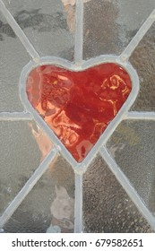 A red heart and clear stained glass window, in the white front door of a house in Looe in Cornwall