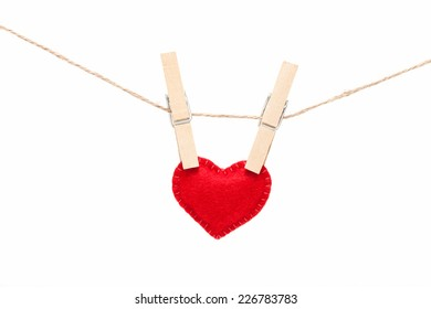Red heart with clothespins hanging on clothesline isolated on white background. Valentines Day