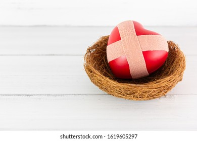 Red Heart with Cross Plaster inside bird nest on white wood background. Protect Pain of Love with Copy Space.