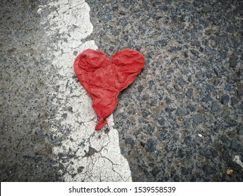 Red heart. Deflated red balloon in the shape of a heart, found lying in the road.