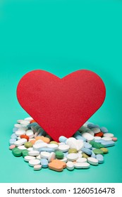 Red heart with different pills, bright green background