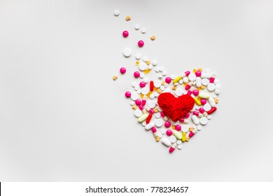 red heart with different pills over white background, healthy life concept.heart disease, heart condition. Problems with health. Arrhythmia, heart failure.Copy space