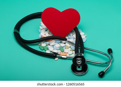Red heart with different pills, and stethoscope bright green background