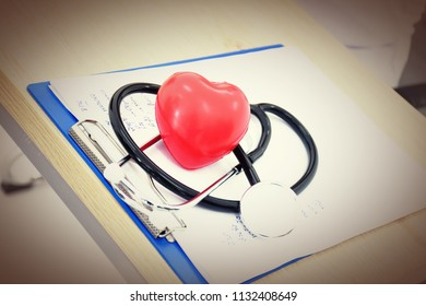 Red heart doctor's head placed on paper in the room.
