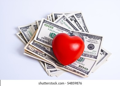 red heart and dollar bills on white background
