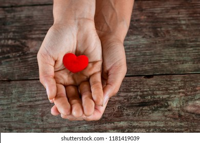 red heart in female hand on wooden background.