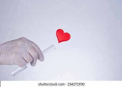 Red heart flowing out of a laboratory test tube, concept, close up