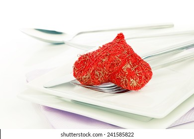 Red heart with fork. Concept image for Valentine dinner/love food/love cooking etc. Copy space.