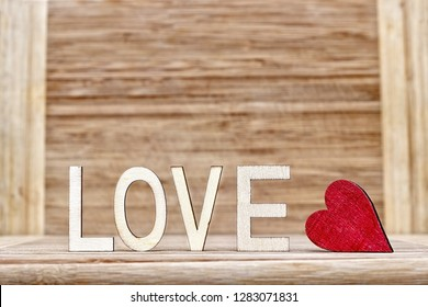 A red heart in front of a wood background and the inscription LOVE