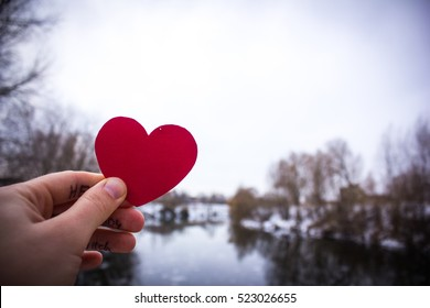 red heart in the hand of the girl. background river. St. Valentine's Day
