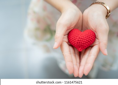 Red heart in hands from above. Healthy, love, donation organ, donor, hope and cardiology concept. Valentines day card.Giving love concept with hands holding a red heart.
