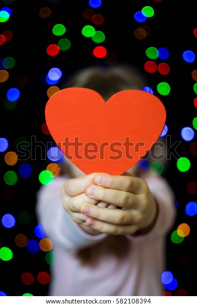 red heart in the hands of a child