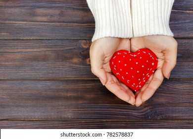 red heart in hands closeup on wooden background.
