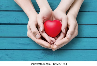 Red Heart in hands, close-up view