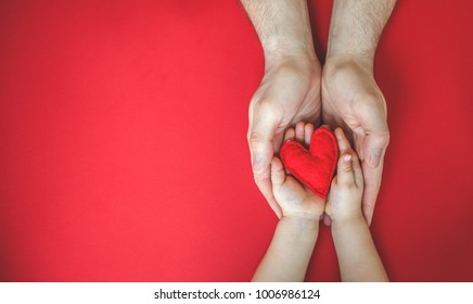 Red heart in hands - dad and child. Valentine's day. Mother's Day. Love and health care. Family insurance.