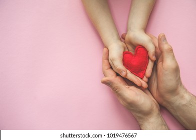 Red heart in hands - mother or dad and child. Hands in hands with red heart. Valentine's day. Mother's Day. Love and health care. Family insurance.