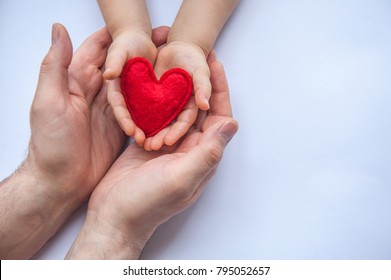 Red heart in hands - mother or dad and child. Valentine's day. Mother's Day. Love and health care.  Family insurance.