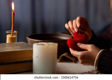 Red heart in hands of witch, love spell and broken heart, unrequited love. Psychic vision, fortune teller.