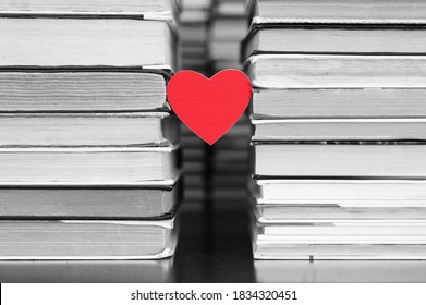 A red heart hangs between the stacks of books in the library. Heart colored, books and black and white background. Book reading concept