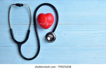 Red heart with heartbeat or heart rate and stethoscope on blue wooden background. Copy space. Medical and Health care, Valentines day.